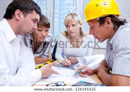 Meeting the team of engineers working on a construction project at the table - stock photo