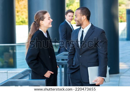 Meeting two businessmen. Two businessman talking on the street standing facing each other while their colleague comes up to them in the background - stock photo