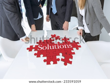 Meeting with people around a table with a puzzle with the words solutions - stock photo