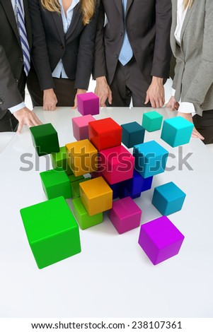 Meeting with people around a table with multicolored blocks floating around - stock photo