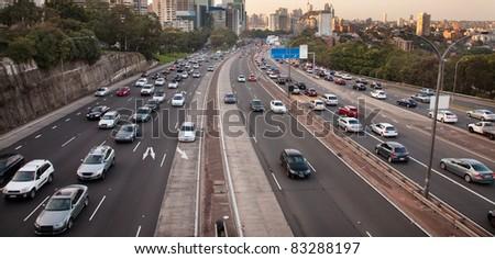 mega-polis highway many lanes full of speeding transport passenger cars commuting people - stock photo