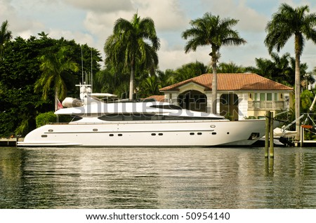 mega-yacht docked outside a mansion on the water - stock photo