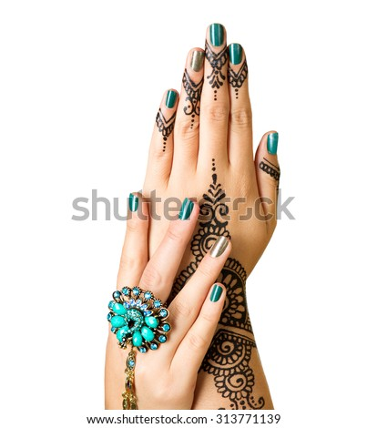 Mehndi tattoo isolated on white. Woman Hands with black henna tattoos. Hands of Indian bride girl with mehndi and perfect emerald manicure and emerald Indian jewels. India national traditions - stock photo
