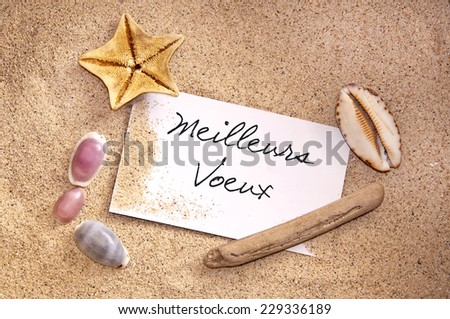 Meilleurs Voeux, meaning happy new year in French, written on a note in the sand with seashells - stock photo
