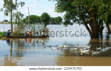 MEKONG DELTA, VIET NAM- SEPT 19: Group of unidentified child sitting on row boat, man rowing on river during flood season, beautiful landscape of Vietnamese countryside,Vietnam,Sept 19, 2014