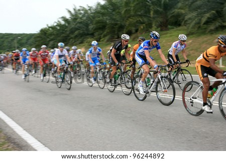 MELAKA, MALAYSIA - FEBRUARY 26 : The largest group of cyclists from various teams cycle compete during Stage 3 of the Tour de Langkawi from Melaka to Parit Sulong on February 26, 2012 in Melaka, Malaysia. - stock photo