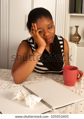 Melancholic african woman writing a letter at home - stock photo