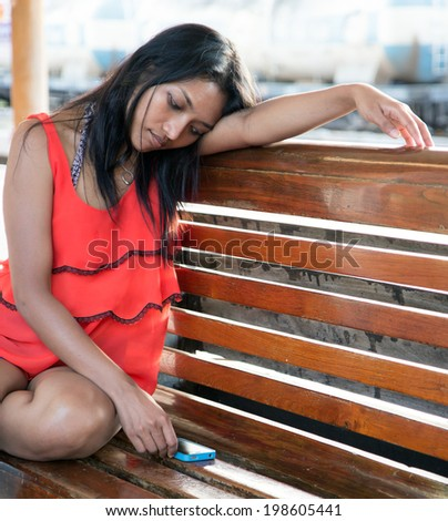 Melancholic girl sitting on a bench at the train station. Bored Passengers waiting at the railway station. Asian girl is sad. Woman resting on a wooden bench on platform.