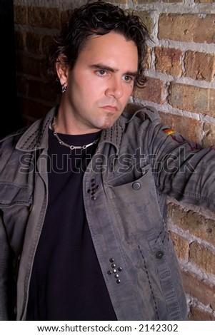 Melancholic portrait of man on brick wall - stock photo