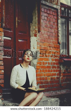 Melancholic woman in classic dress seat near old brick building and read book. Toning photo