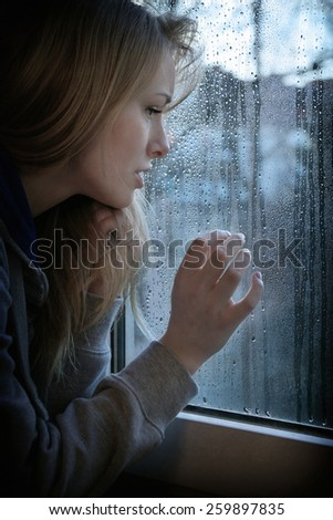 melancholic young woman looking through window with raindrops with added filter grain and vignette                                - stock photo