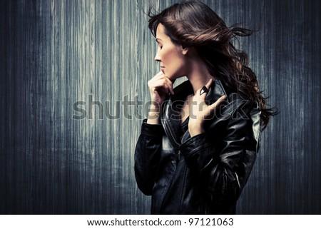 melancholy adult woman in black leather  jacket profile portrait - stock photo