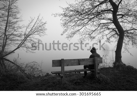 Melancholy emotions concept: sad man sitting on a bench at a foggy lake. - stock photo