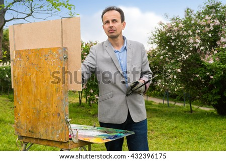 Melancholy handsome middle-aged  male artist painting a masterpiece   on a trestle and easel painting during an art class in a forest - stock photo