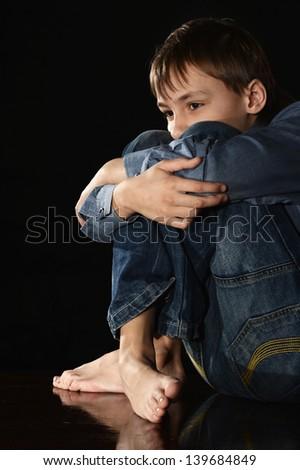 melancholy little boy on a black background - stock photo