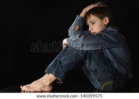 melancholy little boy on a black background