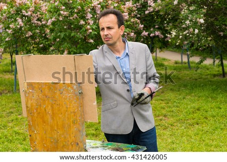 Melancholy male painter painting a masterpiece on a trestle and easel painting during an art class in a park - stock photo