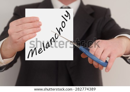 Melancholy, man in suit cutting text on paper with scissors - stock photo