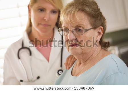 Melancholy Senior Adult Woman Being Consoled by Female Doctor or Nurse. - stock photo