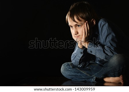 melancholy young boy on a black background - stock photo