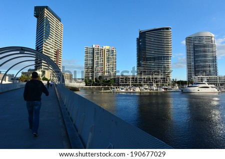 MELBOURNE - APR 14 2014:New towers and bridge rises above the Yarra river in Docklands Melbourne.The development of Melbourne Docklands is one of the largest urban renewal projects in Australia. - stock photo