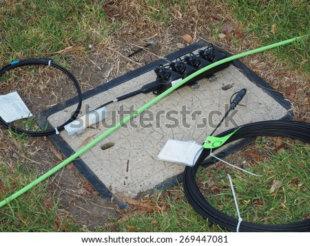 Melbourne, Australia - 2015, April 10: Road side pit with green feeder cable, 8 port multiport and drop cable used for the installation of the National Broadband Network in Australia