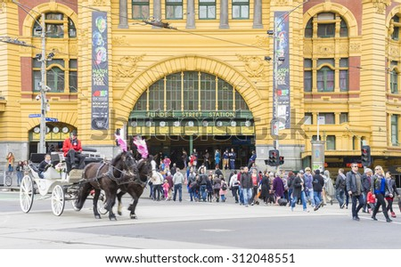 Melbourne, Australia - August 29, 2015: Horse-drawn carriage and commuters outside the Flinders Street Station in Melbourne.  - stock photo
