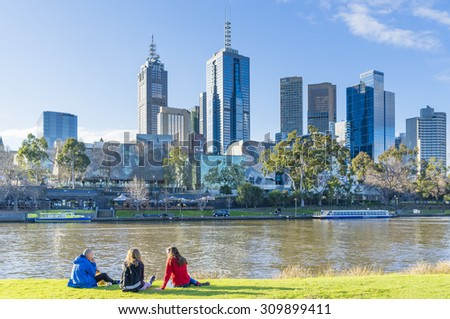 Melbourne, Australia - August 15, 2015: People sitting on Banks of Yarra River in Melbourne near sunset with cityscape as the background.  - stock photo