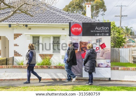 Melbourne, Australia - August 30, 2015: People walking past an auction sign on display outside a house in Melbourne during daytime. - stock photo