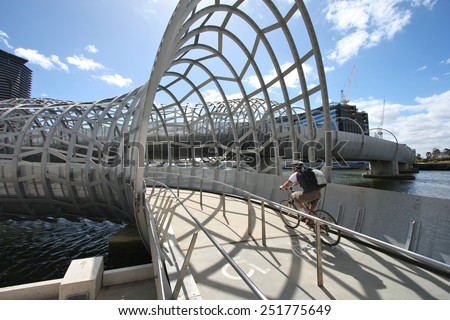 MELBOURNE, AUSTRALIA - FEBRUARY 9, 2009: Cyclist rides along Webb Bridge in Melbourne, Australia. Webb Bridge was designed by D.C. Marshall and received many awards. - stock photo