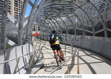 MELBOURNE, AUSTRALIA - FEBRUARY 9: Cyclist rides along Webb Bridge on February 9, 2008 in Melbourne, Australia. Webb Bridge was designed by D.C. Marshall and received many awards. - stock photo