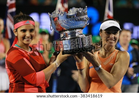 MELBOURNE, AUSTRALIA - JANUARY 30, 2016: Grand Slam champion Sania Mirza of India (L) and  Martina Hingis of Switzerland during trophy presentation after doubles final match at Australian Open 2016 - stock photo