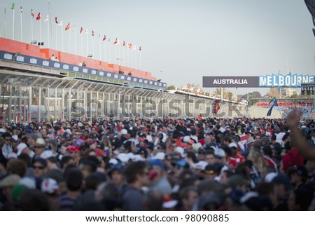 MELBOURNE, AUSTRALIA - MARCH 18: The crowd floods the circuit to watch the podium and results of the 2012 Qantas Australian Grand Prix on March 18, 2012 in Melbourne, Australia - stock photo