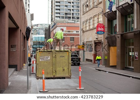Melbourne, Australia-September 12, 2012. Construction workers loadding waste into an industrial waste bin in a side alley, Melbourne, Victoria, Australai