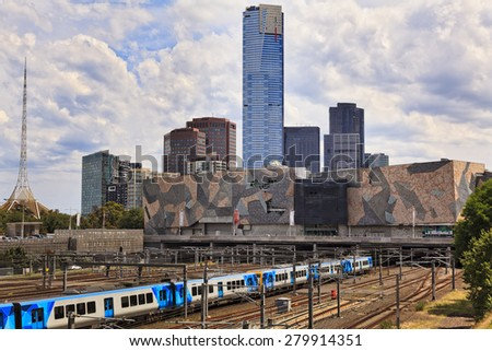 Melbourne CBD cityscape towards flinders train station with metro train coming in railway surrounded by tall skyscraper towers of modern architecture - stock photo