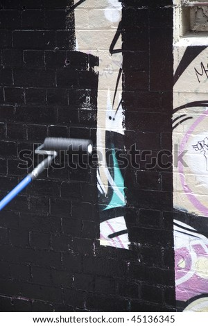Melbourne illegal street graffiti being painted over - stock photo