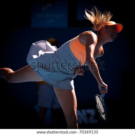 MELBOURNE - JANUARY 19: Maria Sharapova of Russia in her second round win over Virginie Razzano of France in the 2011 Australian Open - January 19, 2011 in Melbourne - stock photo