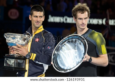 MELBOURNE - JANUARY 27: Runner-up Andy Murray of Scotland (R) is watched by winner Novak Djokocvic   at the trophy presentation at the 2013 Australian Open  on January27, 2013 in Melbourne, Australia. - stock photo