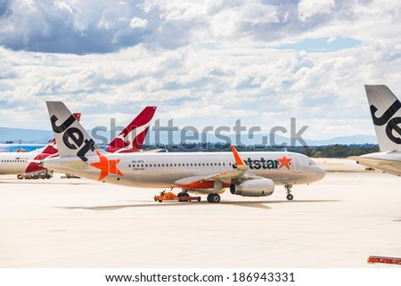 MELBOURNE, VICTORIA/AUSTRALIA, MARCH 17TH: Image of a Jetstar passenger airliner taxiing and Qantas airliner at Melbourne Airport on 17th March, 2014 in Melbourne - stock photo