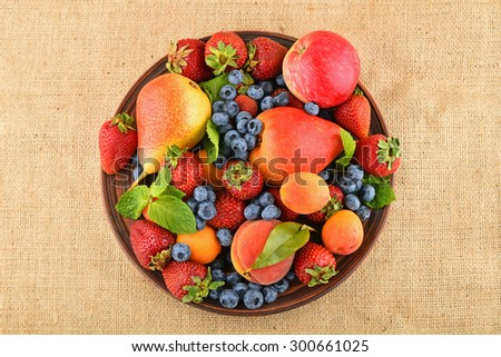 Mellow fresh summer fruits and berries mix with mint leaves in ceramic plate on burlap jute canvas, strawberries, blueberries, apricots, peach, apple and pear - stock photo