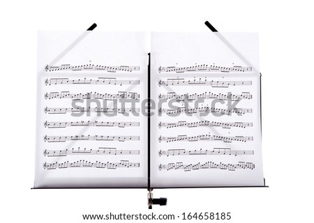 Melody sheets on a music sheet stand isolated in white - stock photo