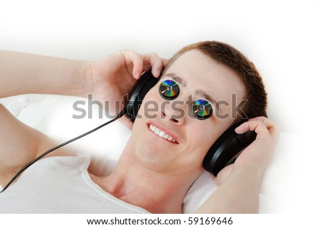Meloman with headphones and music cds on his eyes - stock photo