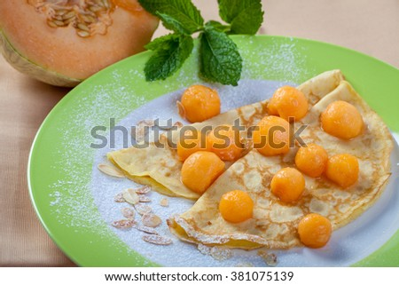 melon balls on crepes with peppermint leaves and almonds