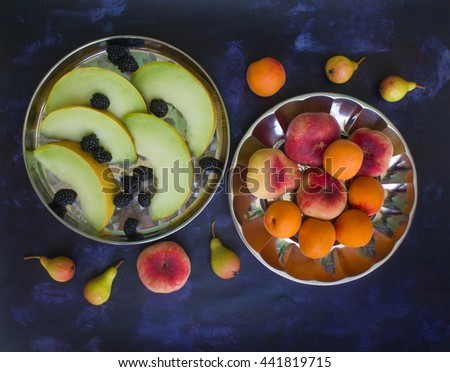 Melon, blackberries, apples, peaches and pears on a dark background - stock photo