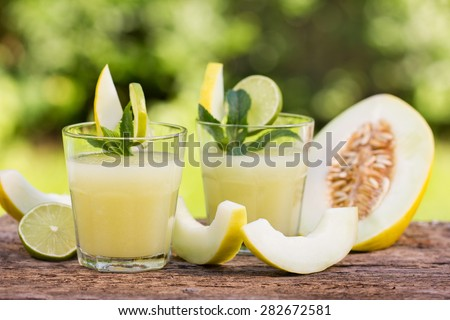 Melon juice in the glass on the wooden table - stock photo
