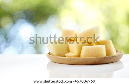 melon slice on wooden plate with white background