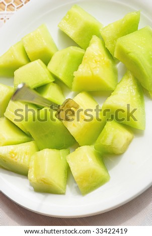 Melon slices and spoon in plate - stock photo