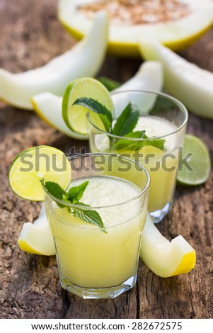 Melon smoothies with slices of melon on the wooden table - stock photo