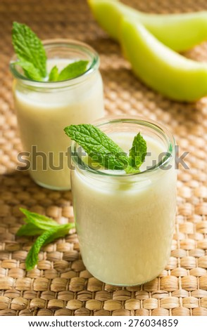 Melon smoothies, yogurt in a glass jar in the background melon slices , mint leaves in a frame. Melon smoothies. Melon yogurt. Close-up. Vertical shot. - stock photo