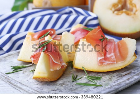 Melon with prosciutto of Parma ham on wooden table, closeup - stock photo